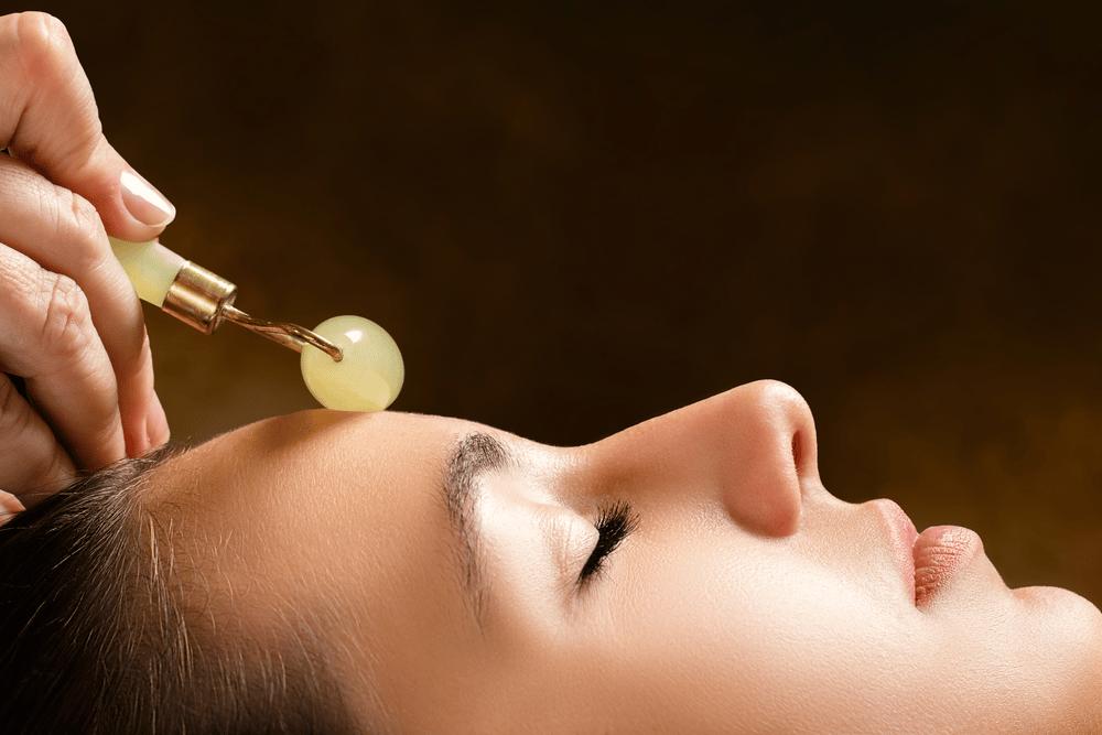 massage facial à l'aide d'un rouleau de jade